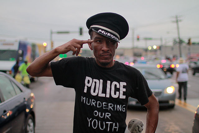 August 15, 2014- Ferguson, Mo.- A protester walks the streets of Ferguson, Mo., in a mock police officer's uniform. 8/15/2014 Photo by Dave Gershgorn/ NYCity Photo Wire