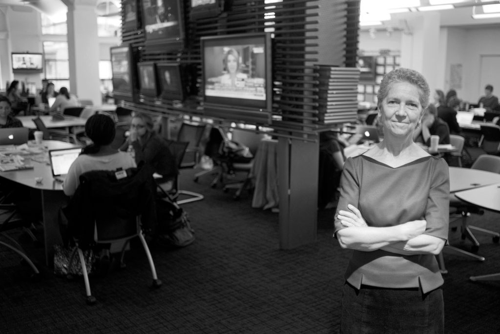 Photo of Dean Sarah Bartlett with her arms crossed standing in the school's newsroom.