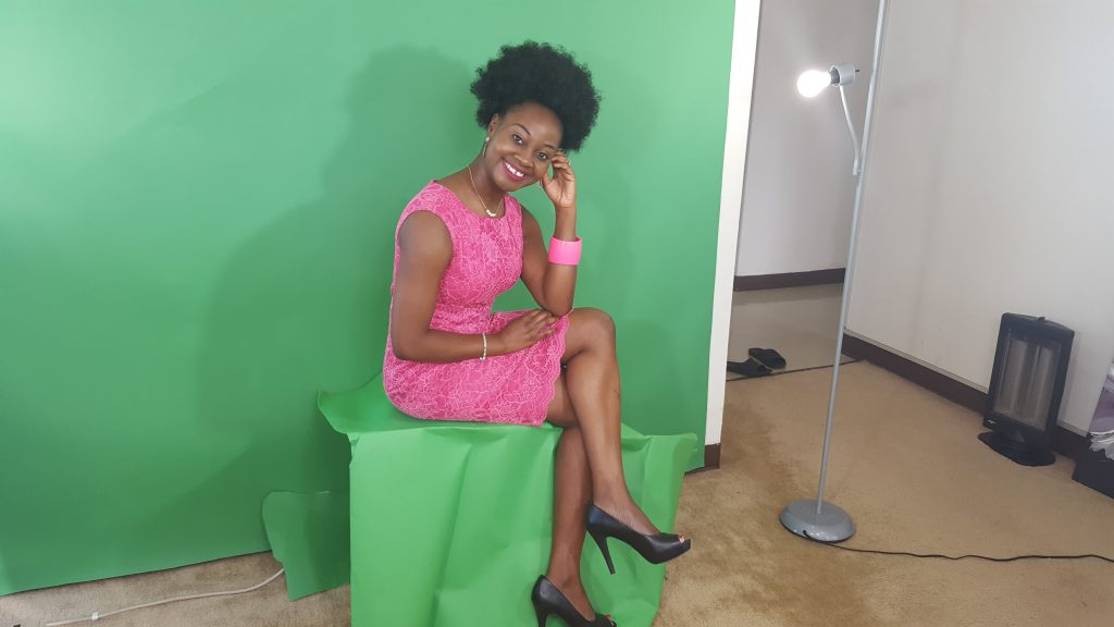 Alum Adeola Fayehum poses seated in front of a green screen.