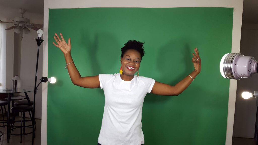 Alum Adeola Fayehun appears in front of a green screen smiling with her eyes closed and hands up.