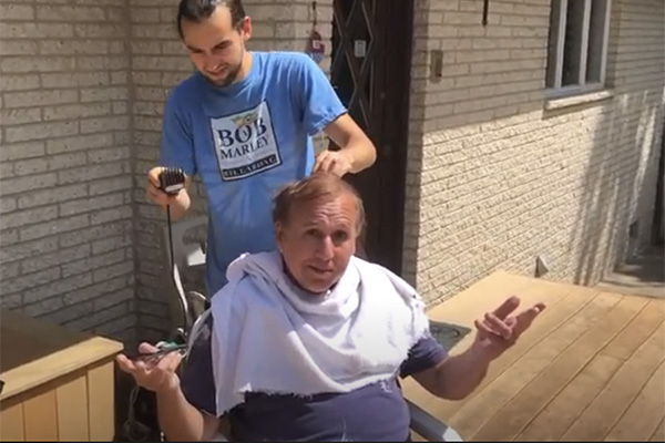 Adjunct professor Michael Lysak getting a haircut from his son at home.
